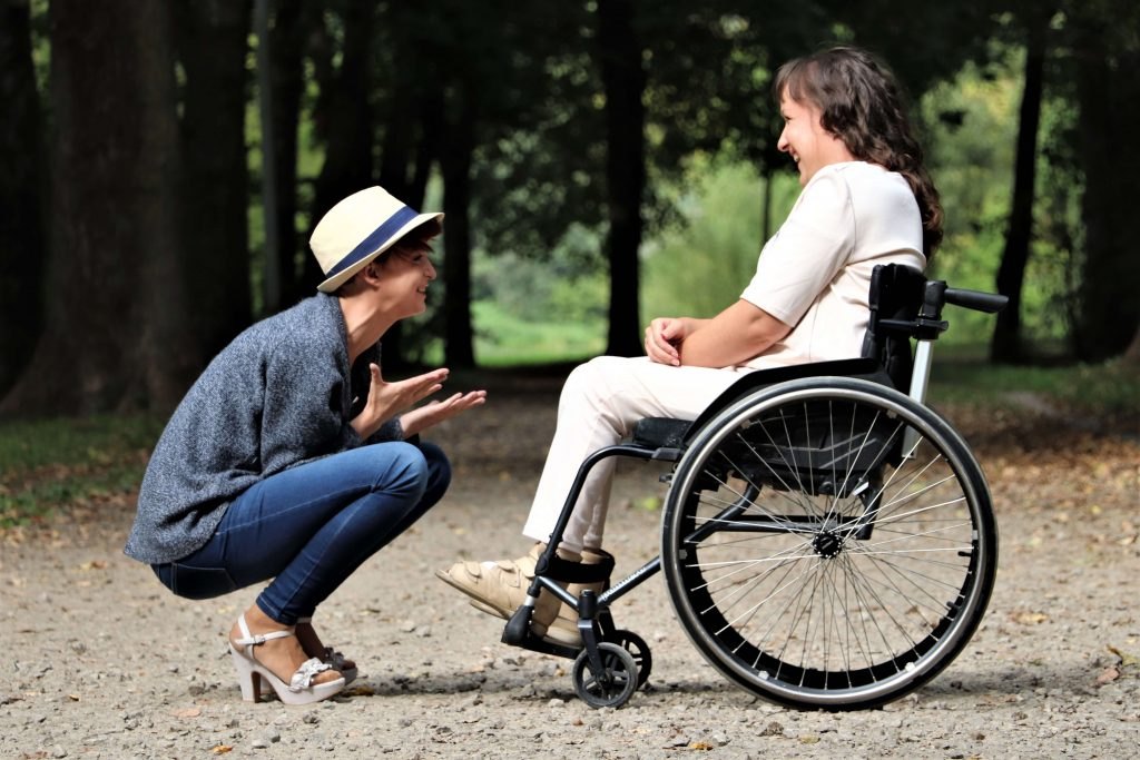 persona in sedia a rotelle con amica